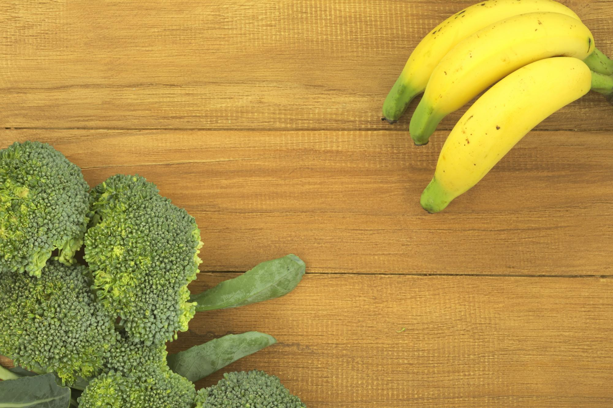 bananas and broccoli on wooden surface