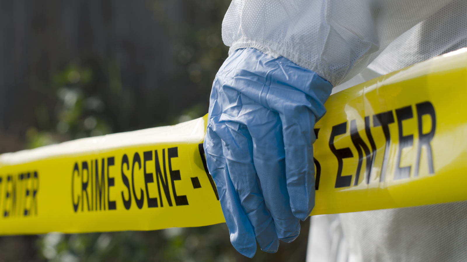 Yellow crime scene tape held by gloved hand